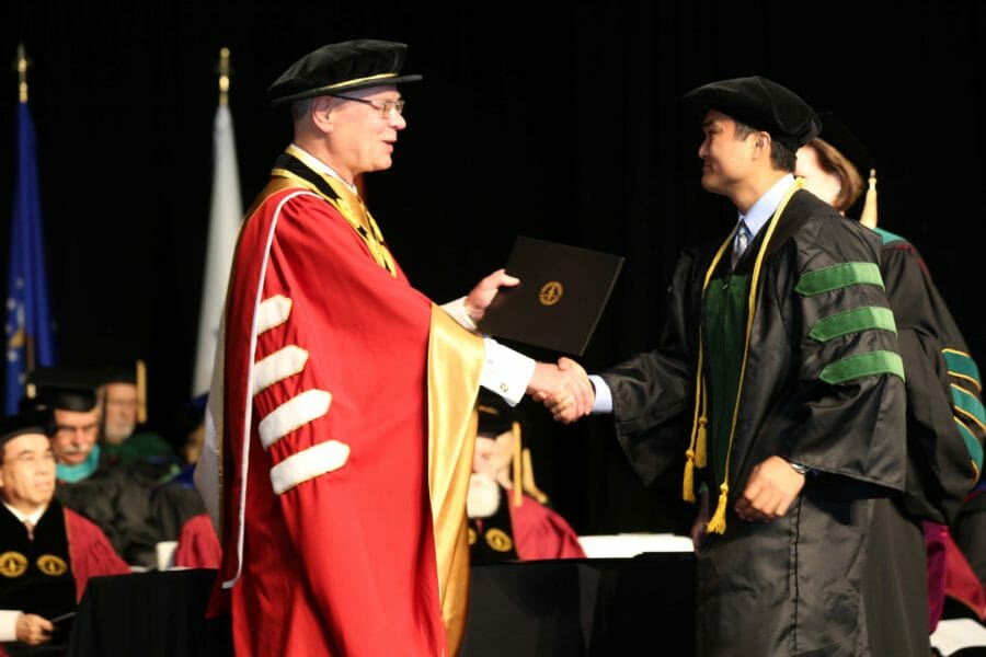 DO graduate shaking President Wilson's hand while receiving their dimploma