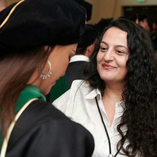 A Commencement assistant helps a graduate prepare for the ceremony.