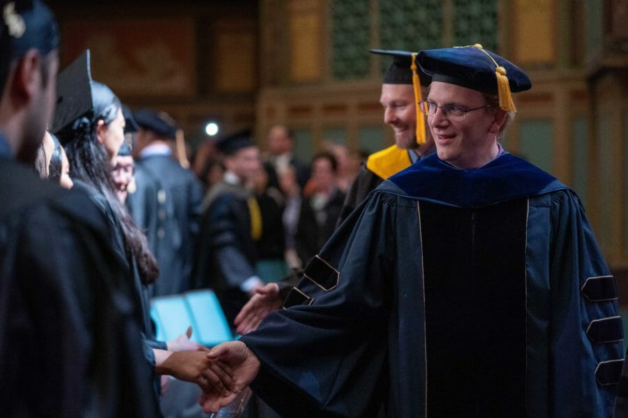 WesternU faculty shaking graduates' hands as they process to the PCA stage