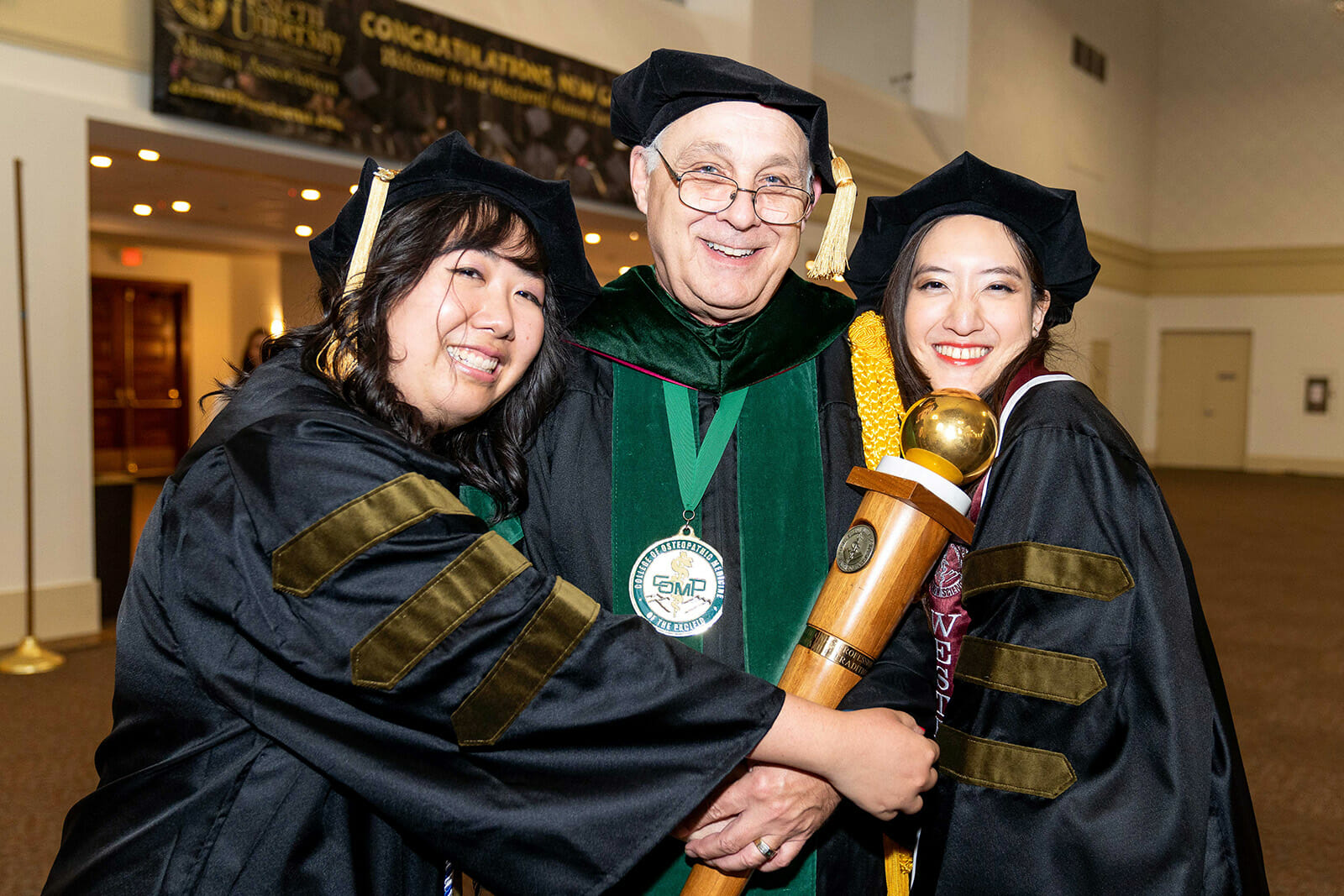 Two PharmD graduates posing with Dr. Cundari the University Marshal